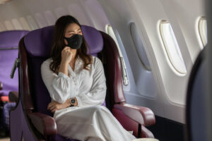 A woman wearing a mask while traveling