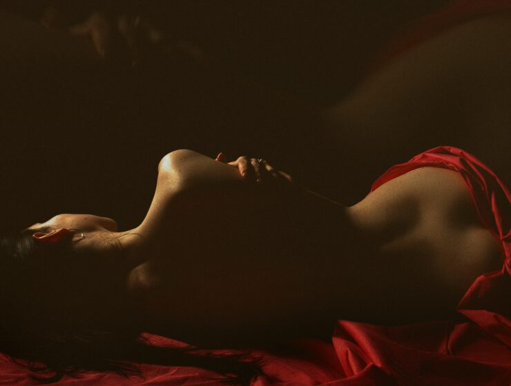 A woman lying in a bed with red sheets.