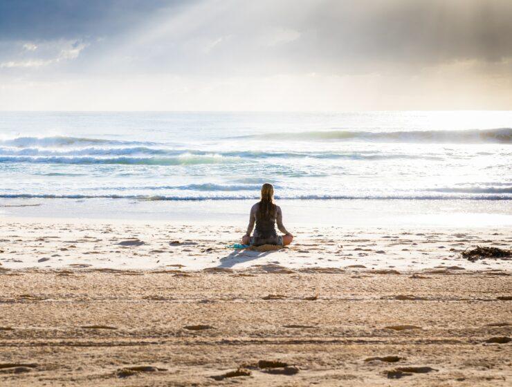 A woman meditating on the beach